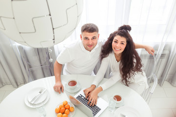Happy young couple with laptop sitting at dining table in kitchen or living room at modern home