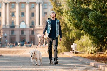 Handsome young hipster with dog outdoors