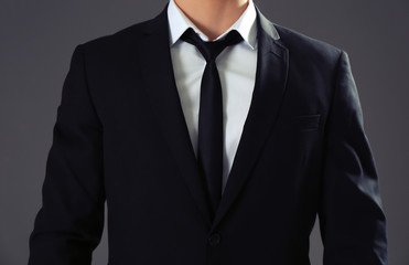 Handsome man in formal suit on grey background, closeup