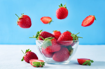 Fresh strawberries in a glass bowl with flying slices