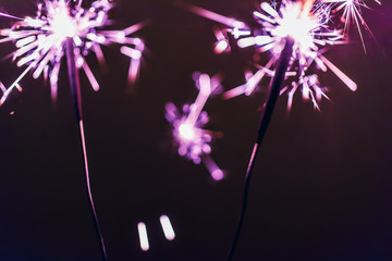 lilac bengal  sparkler lights on a black background in honor of Christmas and New Year and birthday...