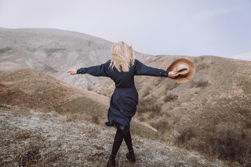 stylish blond girl in blue dress and with beige hat in hands is standing with her back in the mountains on nature with beautiful view and scandinavian landscape