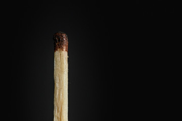 The match is not completely burned, substandard on a black background closeup
