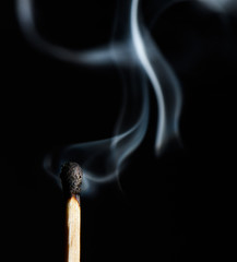 The burnt head of the match with a thick smoke close up on black background