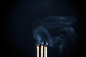 Three matches with burnt heads emitting the last effort of the remnants of smoke on black background