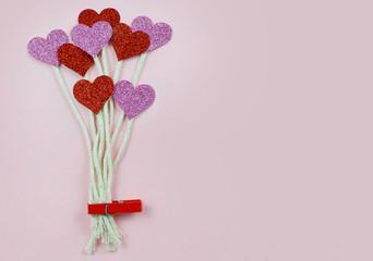 Sparkly red and pink hearts on strings like balloons, clipped with red clothespin on soft pink background. Copy space.
