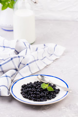 The plate of fresh organic blueberry with bottle of milk on a white background