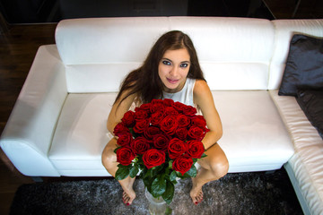 Attractive woman with long brown hair is holding a luxurious bunch of red roses. She wears short dress and sitting barefoot on white leather sofa in stylish interior