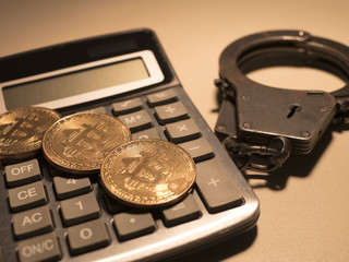 bitcoin calculator and handcuffs on table