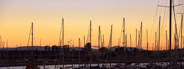 Schiffsmaste im Yachthafen von Valencia vor glühendem Abendhimmel