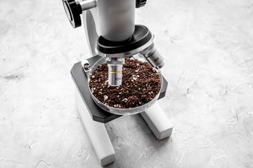Analysis process. Soil under microscope on grey background