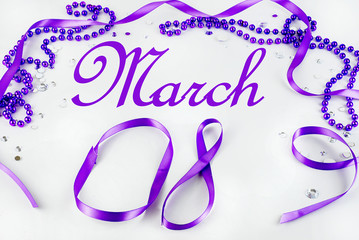 Purple beads and ribbon and sparkly jewels on a light background make a border for International Women's Day on March 8th each year.