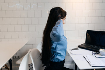 young black-haired freelancer girl in blue shirt working on laptop in cafe
