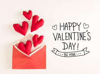 Valentine's Day message with red heart cushions coming out of an envelope