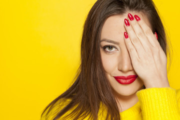 beautiful woman in a yellow blouse, covering her eye with her hand on a yellow background
