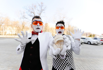 Two mimes in dental glasses are holding a cast of the jaw in their hands. Dental prosthetics