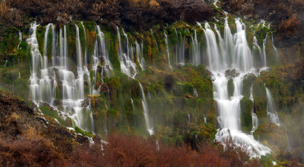 Many springs pour from the side of a mountain cliff in Hagerman Valley Idaho