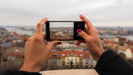Smartphone held by woman hands. Photo of Budapest parliament building on the screen, taken from Fisherman's bastion in BudaPest, Hungary.