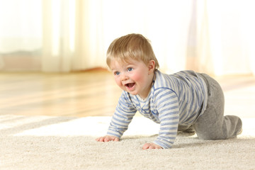 Happy baby crawling and laughing on a carpet