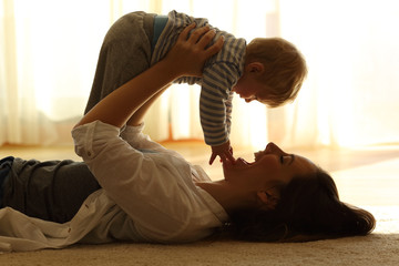 Backlighting of a mother raising her baby at home