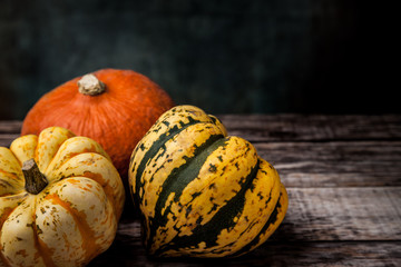 Three colourful various squash on wooden table with dark background