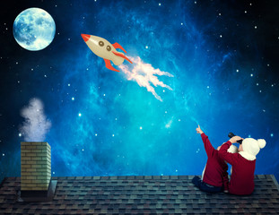 Two brothers on winter night sit on the roof of the house and watch the flight of the rocket in the sky.