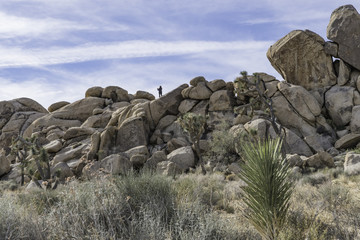 tourist in the Mojave desert in Joshua Tree National Park on the monzogranite rock formations found there