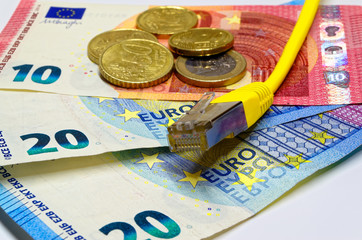 Yellow network communication plug lying on the Euro banknotes