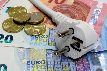 White power plug lying on euro banknotes