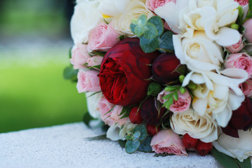 The Bride's Bouquet. Wedding Bouquet. A Bouquet of Red and Pink and Red Roses and Peonnies Flowers on blurred background.