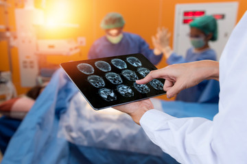 Smart health care internet of things and hospital management technology concept. Doctor using x-ray brain tablet for check status of patient in operating room and surgery doctor in smart hospital.