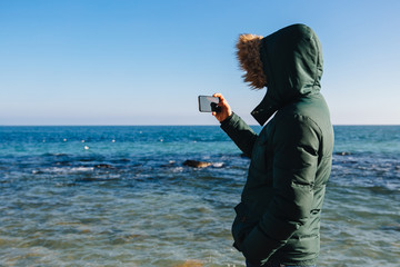 Guy taking a picture of the sea