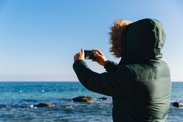 Man taking a picture of the seascape