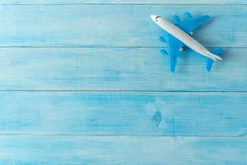 air plane miniature figure on light blue wood plank background