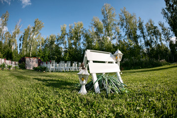Beautiful setting for outdoors wedding ceremony waiting for bride and groom and guests. White chairs decorated with flowers, are in the zone of the wedding ceremony in a forest. copy space