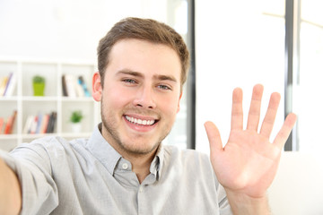Man waving on a video call at home