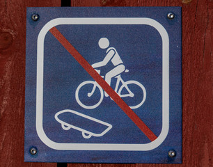No skateboarding and no cycling sign, blue and white sign on red plank wall.