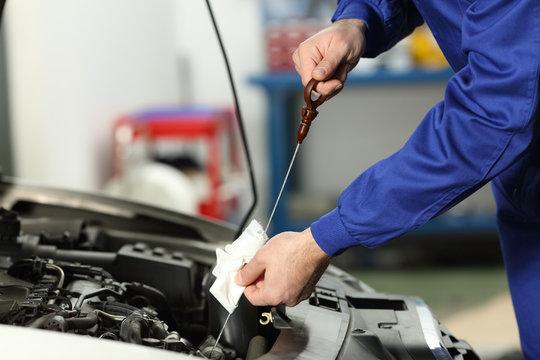 Car mechanic checking oil level