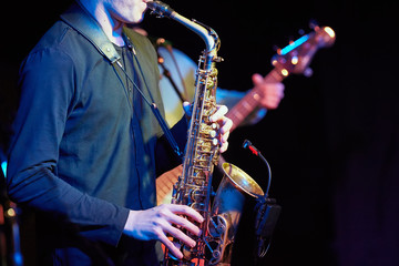 A young guy plays a saxophone with a microphone.