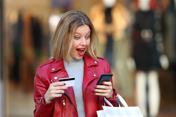 Surprised shopper paying on line in a mall