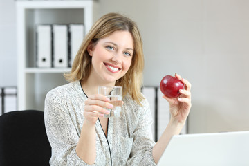 Happy worker posing holding an apple at office