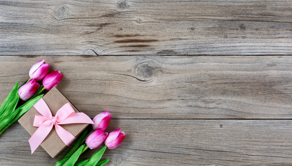 Tulips and gift for Mothers day on rustic wooden background