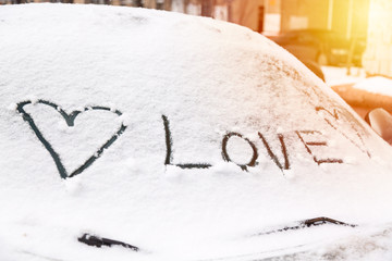Heart sign and love inscription on a car windshield covered with snow