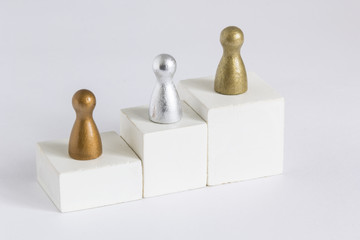 Playful Concepts: Gold, Silver and Bronze gamefigurine on a winner podium