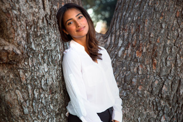 Sweet sincere beautiful woman of mixed ethnicity standing caring for a tree in nature