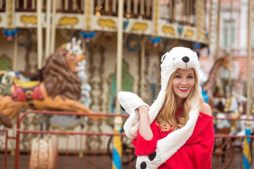 Smiling blonde woman wearing red knitted sweater and funny hat, posing at the background of carousel with lights