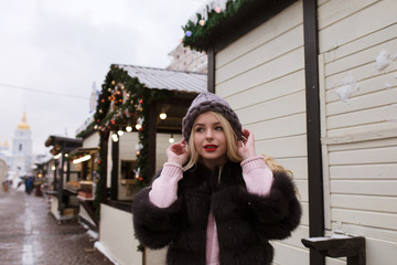 Street portrait of amazing young woman wearing stylish knitted hat and fur coat, posing at the Christmas fair. Empty space