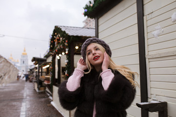 Street portrait of glamorous young woman wearing stylish knitted hat and fur coat, posing at the Christmas fair. Empty space