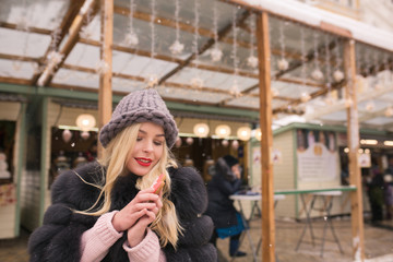Wonderful blonde woman holding flavorous christmas gingerbread against light decoration at the Christmas fair in Kiev