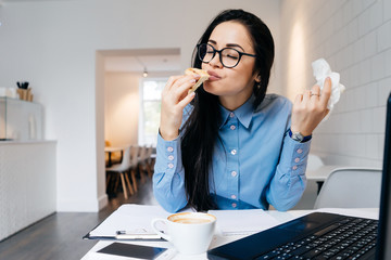 hungry young girl in a blue shirt and glasses is having a sandwich in a cafe